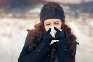 woman blowing her nose outside